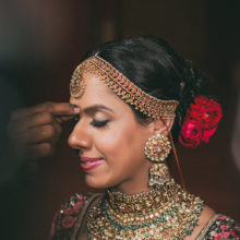sabyasachi bride with red rose in the hair or band baaja bride