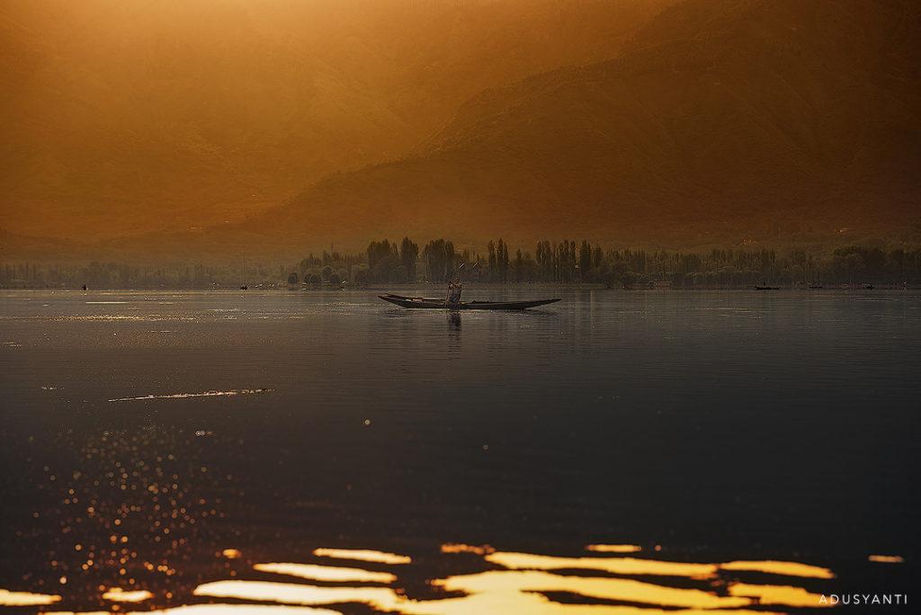 boatman at dal lake during sunset